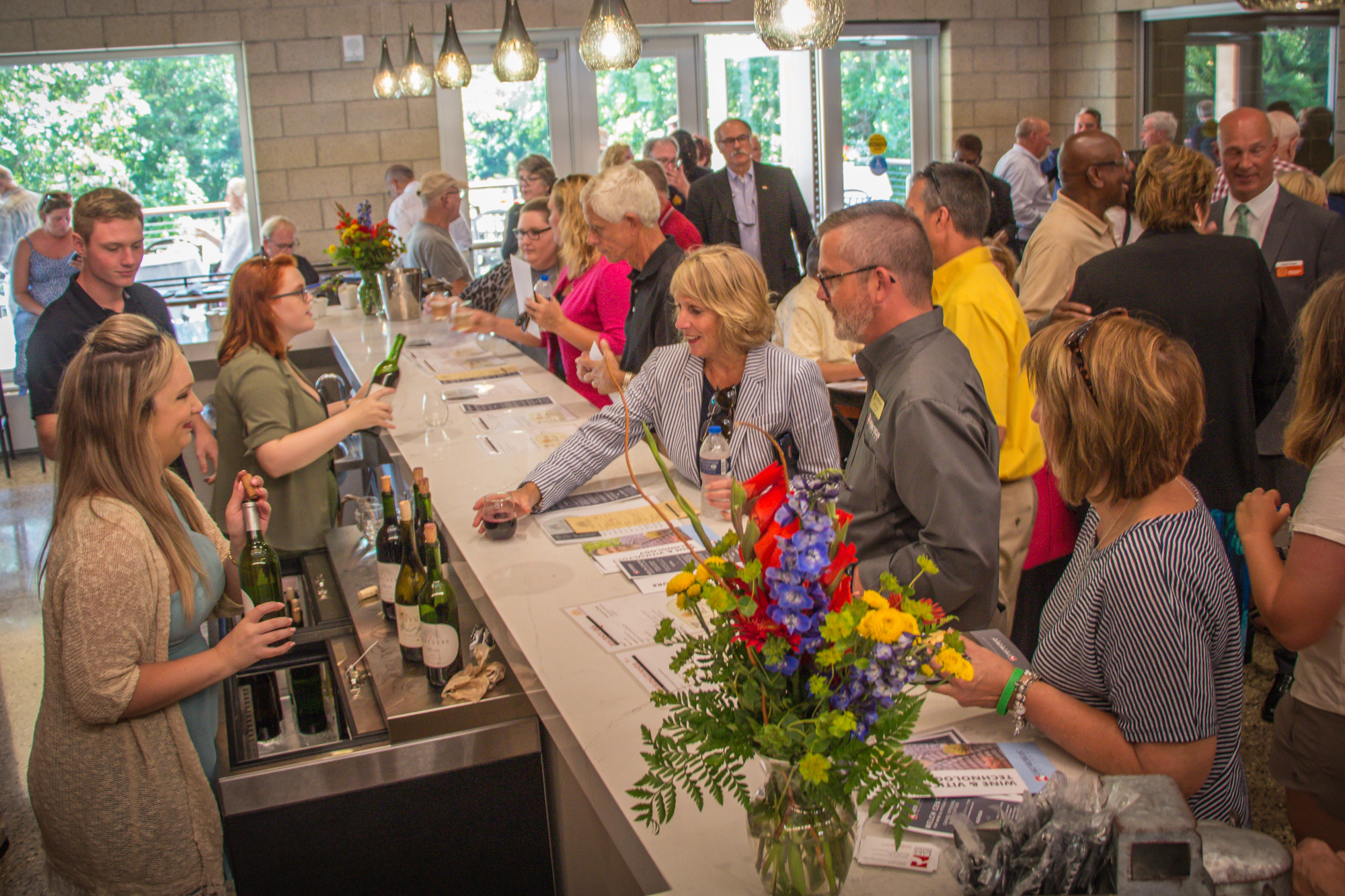 An image showing approximately 30 people at the opening for the Welch Center for Wine & Viticulture Technology. Two people are pouring wine for guests, and there is a vibrant buoquet of flowers on the bar top.