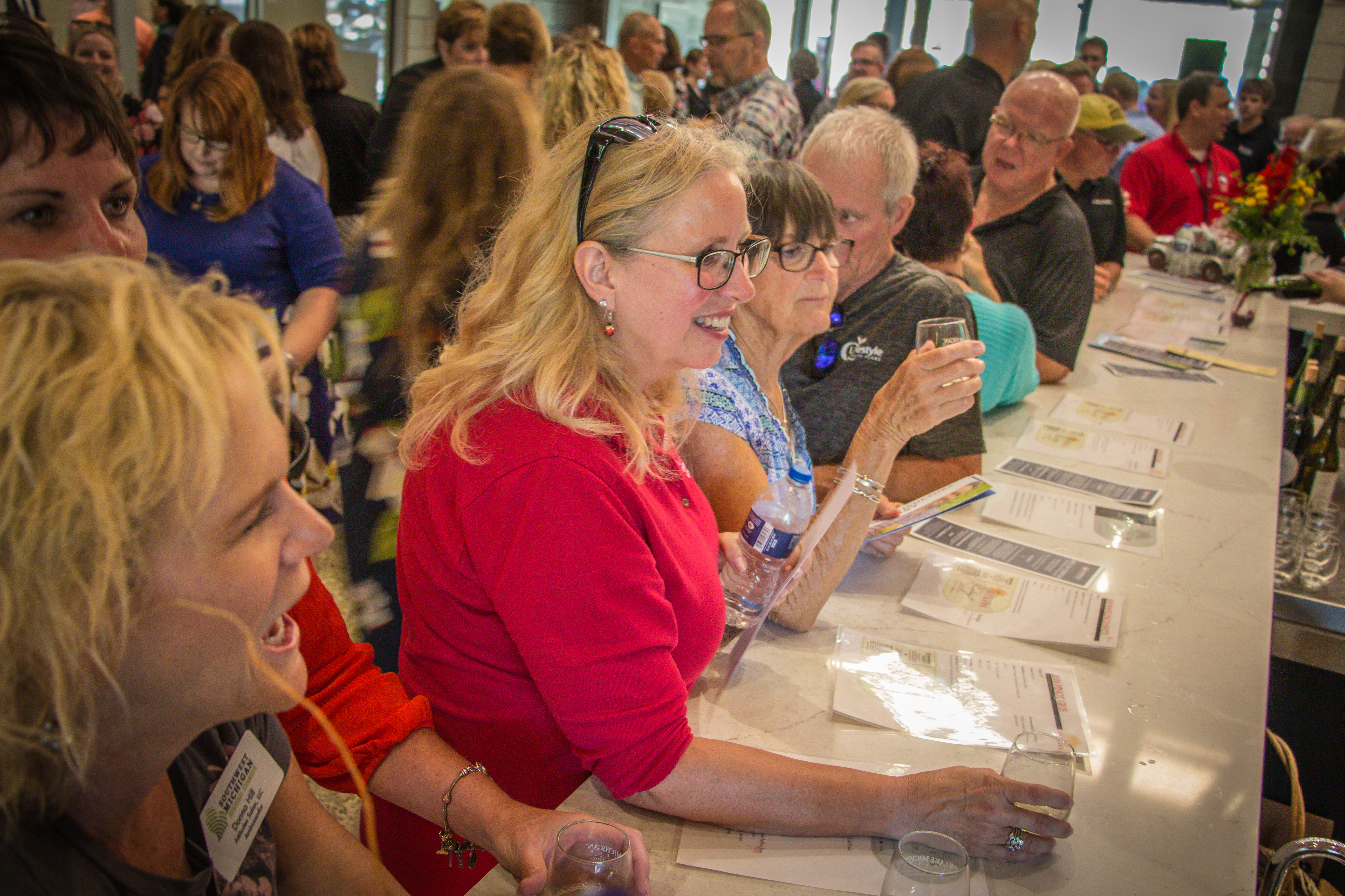 An image showing approximately 30 people at the opening for the Welch Center for Wine & Viticulture Technology. A woman with yellow hair and a red shirt on is holding her glass out to ask for more wine.
