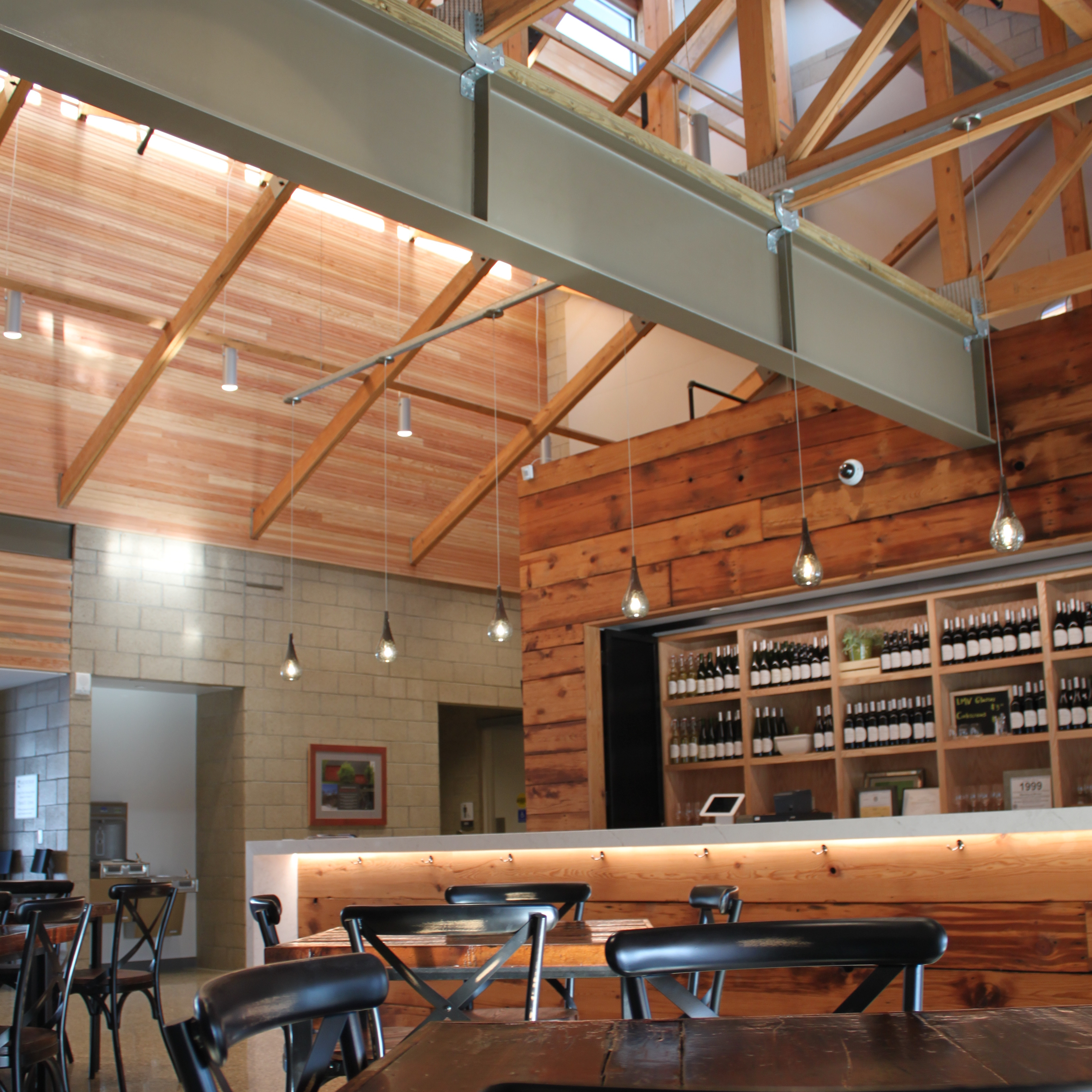 A photo showing the interior of the Lake Michigan Vintners tasting room. A cabinet full of wine bottles and a cinderblock from the back walls. Light pours in from the ceiling across wooden trusses and beams, illuminating wooden tables and a marble bar.
