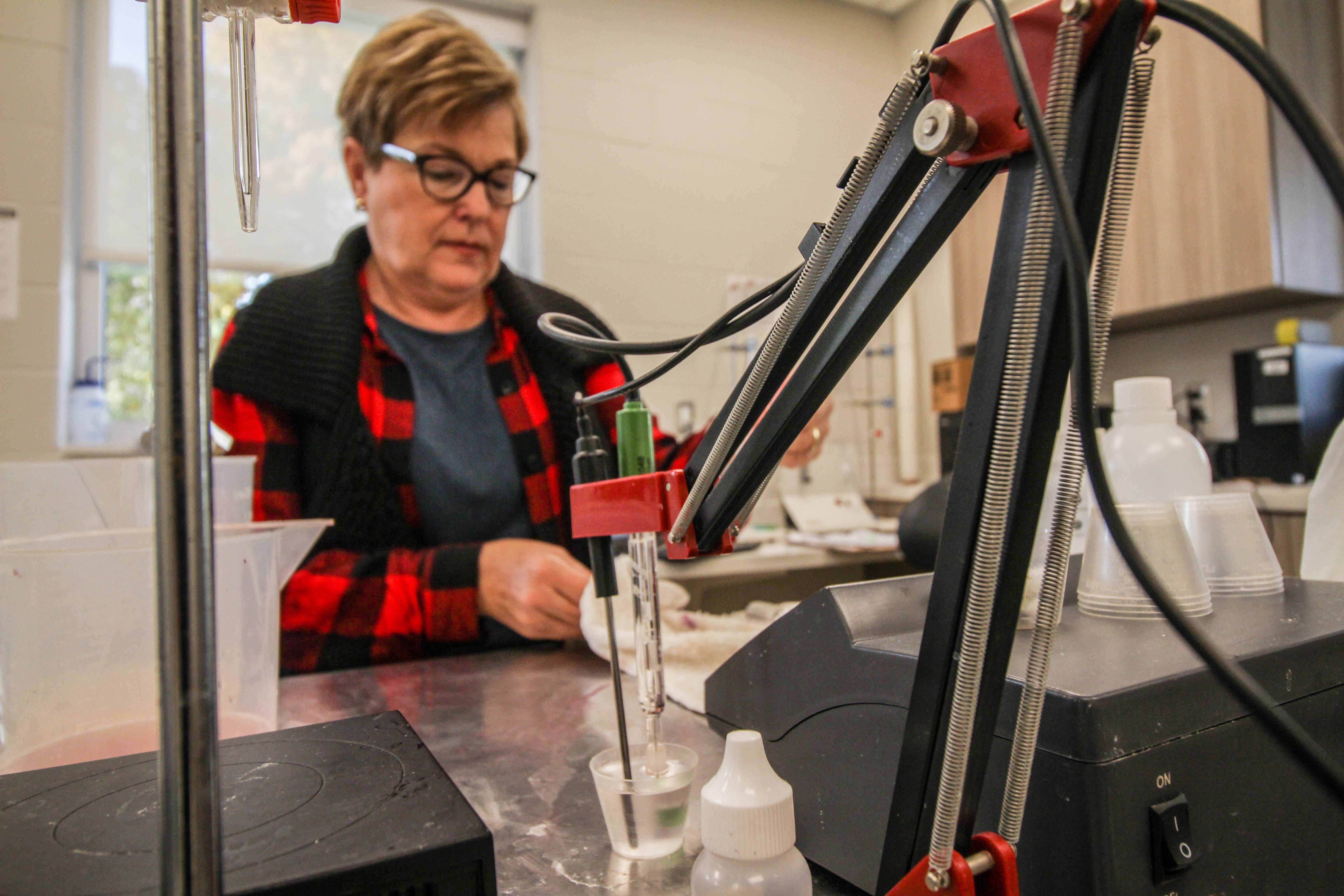 In the background, an older white woman with glasses, brown hair, and a red and black plaid shirt is taking measurements in a laboratory. It is not entirely clear what her hands are doing. In the foreground, there are droppers and equipment for wine titration.