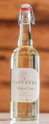 """This image shows a golden 750mL bottle of Lake Michigan Vintners Hard Cider. It reads """"Lake Michigan Vintners Hard Cider, 2018, Lake Michigan Shore. 8.5% alcohol by volume, 750mL."""" The bottle is clear with a swing top cap."""