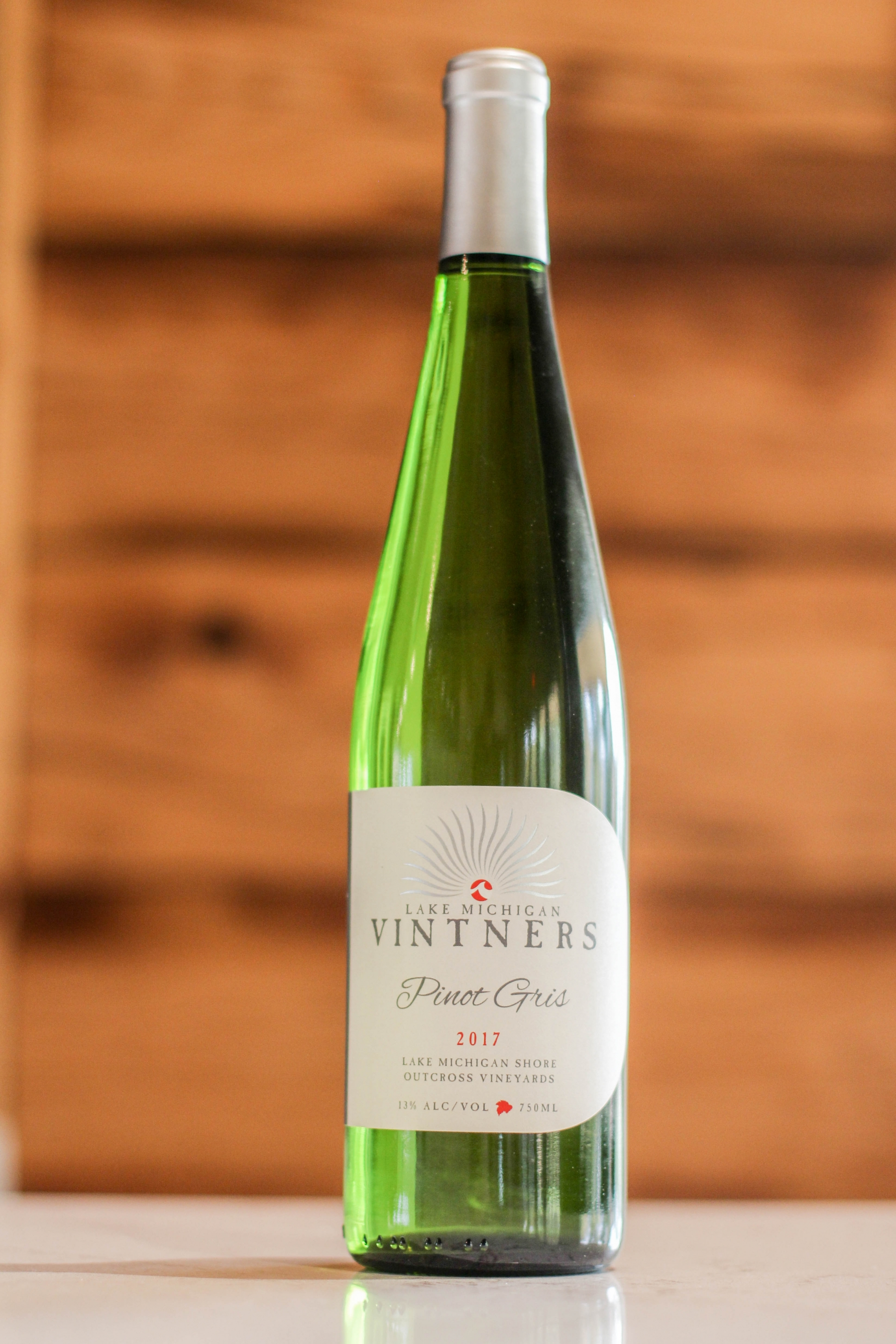 """A close-up of a deep green bottle of Pinot Gris, with a white and silver label reading """"Lake Michigan Vintners, Pinot Gris, 2017. Lake Michigan Shore, Outcross Vineyards. 12% alcohol by volume, 750mL."""" The bottle is a tall Alsace-style bottle."""