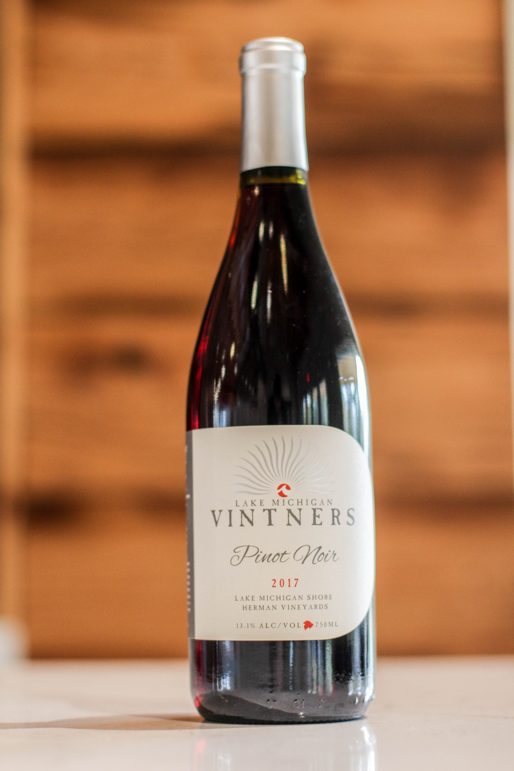 """A close-up of a deep burgundy bottle of Pinot Noir, with a white and silver label reading """"Lake Michigan Vintners, Pinot Noir, 2017. Lake Michigan Shore, Herman Vineyards. 13.1% alcohol by volume, 750mL."""" The bottle is wider and a little shorter than many wine bottles."""