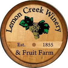 "The Lemon Creek Winery logo shows a barrel with white grapes painted on it, reading ""Lemon Creek WInery & Fruit Farm, Est. 1855."""