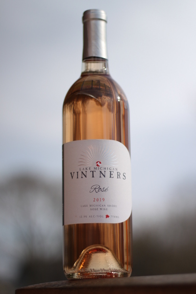 A bottle of pink Rose wine against a partly cloudy sky. The label reads Lake Michigan Vintners, Rose, 2019. Lake Michigan Shore Rose Wine. 12.5% alcohol by volume, 750mL.