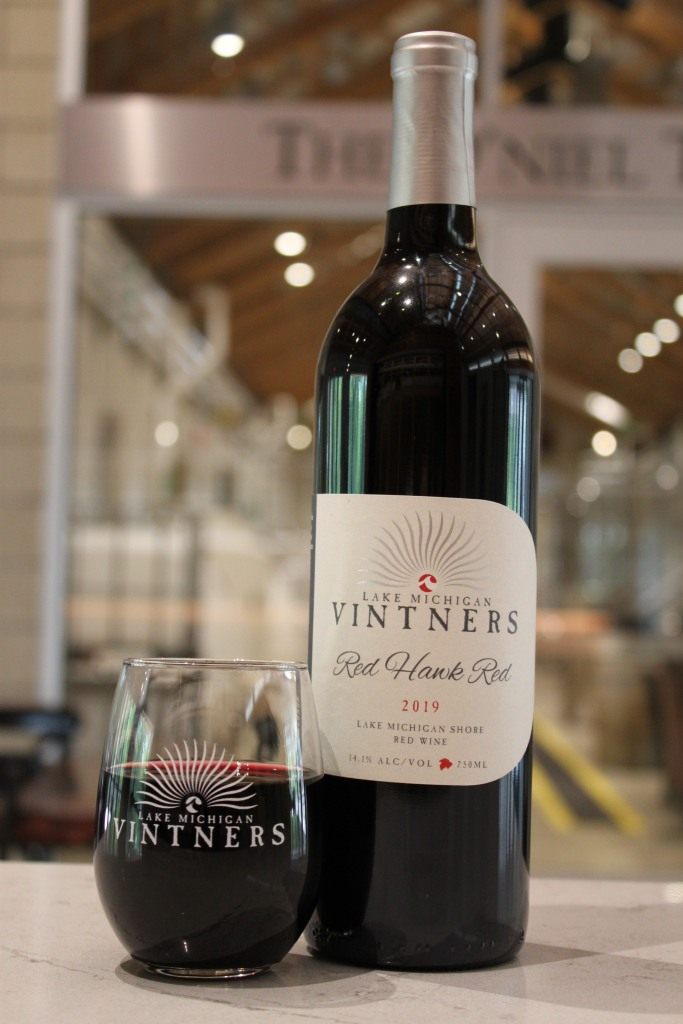 An image of a dark bottle of red wine with a glass of red wine next to it. The glass has an image of a sun on it with the words Lake Michigan Vintners. The bottle has the same image and reads Lake Michigan Vintners, Red Hawk Red, 2019, Lake Michigan Shore Red Wine.